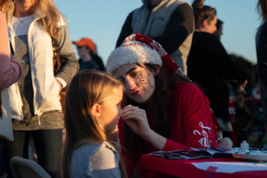 Senior Paige Pakebusch helps out at the face painting booth. (Katie Ray | The Talon News)