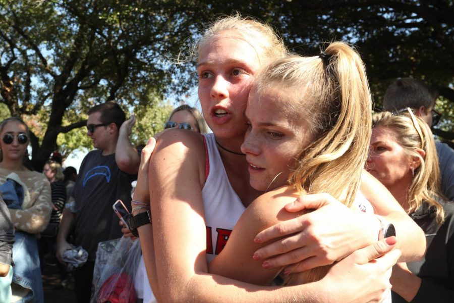 Senior Lanie Rodgers and junior Allie Johnson embrace following the University Interscholastic League (UIL) cross country state tournament. Rodgers led her team to state and has built a community within the program. (Jaclyn Harris | The Talon News)