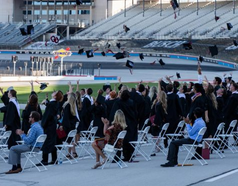 Seniors sit on the track six feet apart from each other while waiting for their turn to walk across stage at the Texas Motor Speedway in Fort Worth, Texas on May 18, 2020. (Alex Daggett / The Talon News)