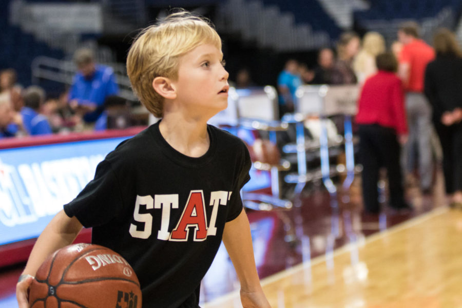 Jett Westmoreland shags the balls to help out the Lady Eagles as they warm up before the game. The team takes on Veteran's Memorial in the UIL State Championship game with a final score of 60-41. (Campbell Wilmot (Campbell Wilmot/ The Talon News)