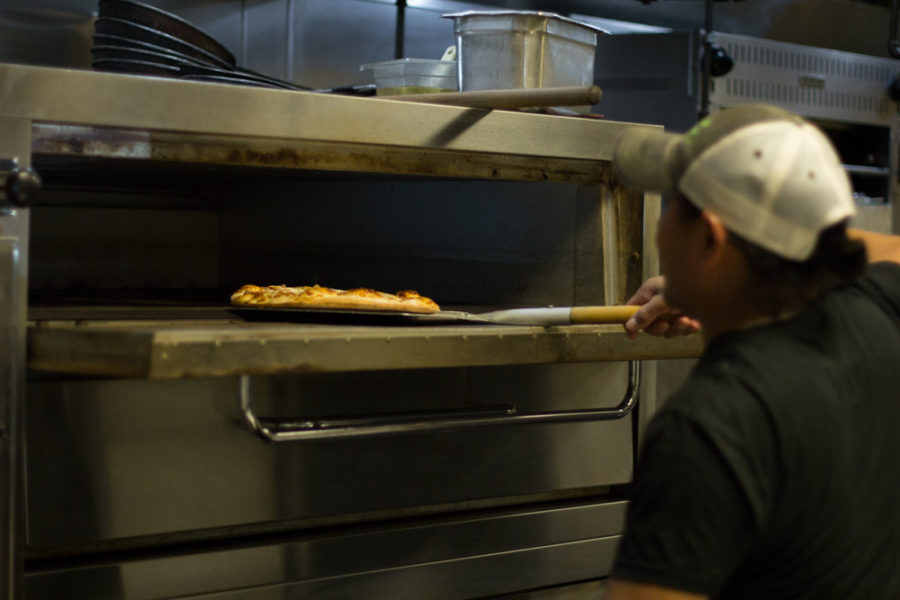 Head cook Amelio Jorges takes out a pizza at Cafe Gecko in Plano, Texas, on Sept. 29, 2018. (Sloan Dial / The Talon News)