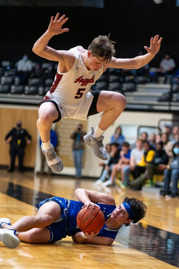 Senior Slate McMellian jumps in an effort to dodge a Lampasas' player as he falls while intercepting the ball on Feb. 25, 2021, in Italy, Texas. (Nicholas West / The Talon News)