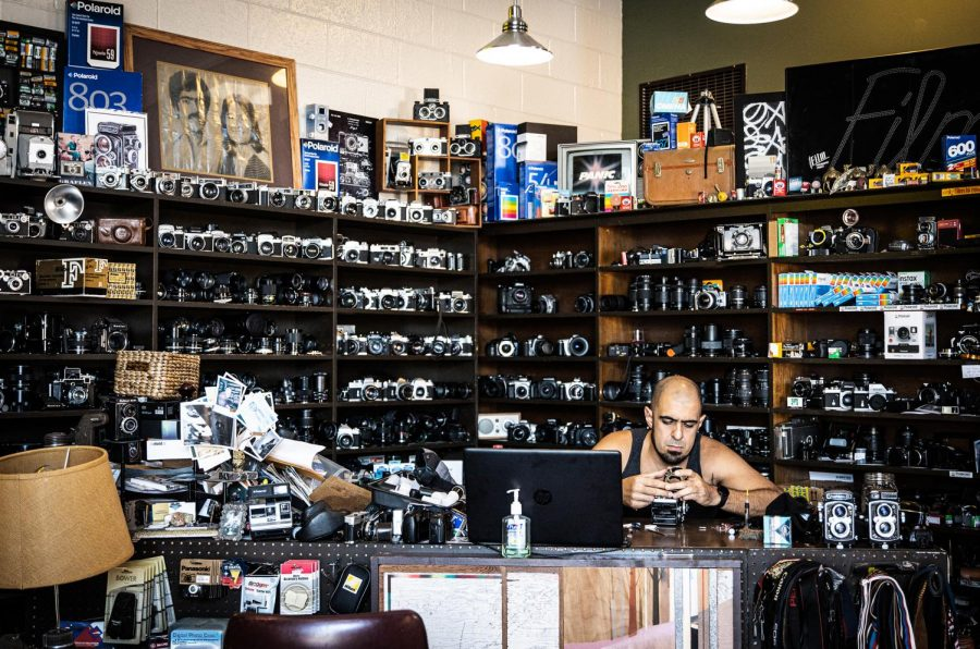 Armand Kohandani works on a Rolleiflex TLR surrounded by his craft at The Denton Camera Exchange in Denton, Texas on Oct. 7, 2020. (Nicholas West / The Talon News)